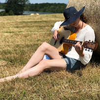 Kerrie leaning against a hay bale in summer writing and playing guitar