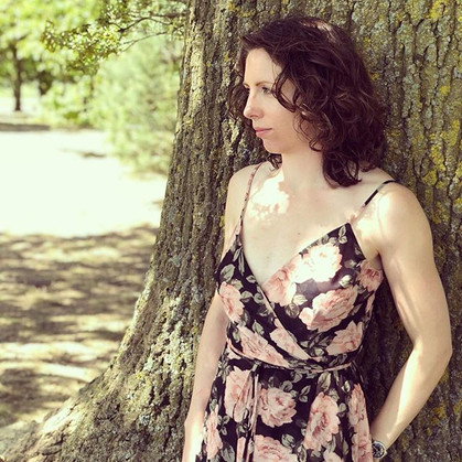 Kerrie leaning against a tree
