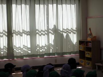 カーテンに、うごめく黒い人影が! 実は園舎耐震工事の技術者さんの影でした。