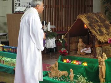 神父さまが、馬小屋の飼い葉桶に、幼子・イエスさまの像を安置します。