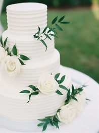 classic white, three tier wedding cake with white roses and greenery