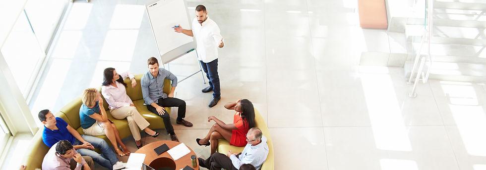 Equipe de várias pessoas está reunida enquanto planejam com o apoio de um quadro.