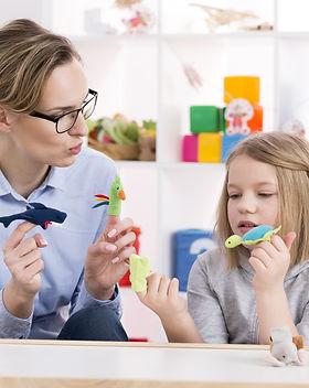 Female teacher using colorful toys durin