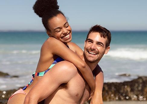 man-giving-piggyback-woman-beach-sunshin