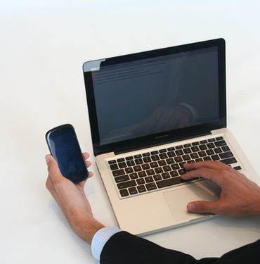 Man holding mobile phone and typing on computer