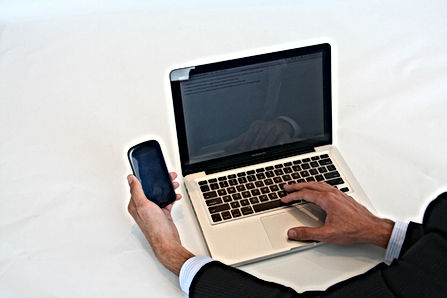 Man using a cell phone and lap top computer