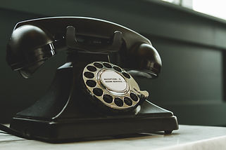 black-rotary-telephone-on-white-surface-