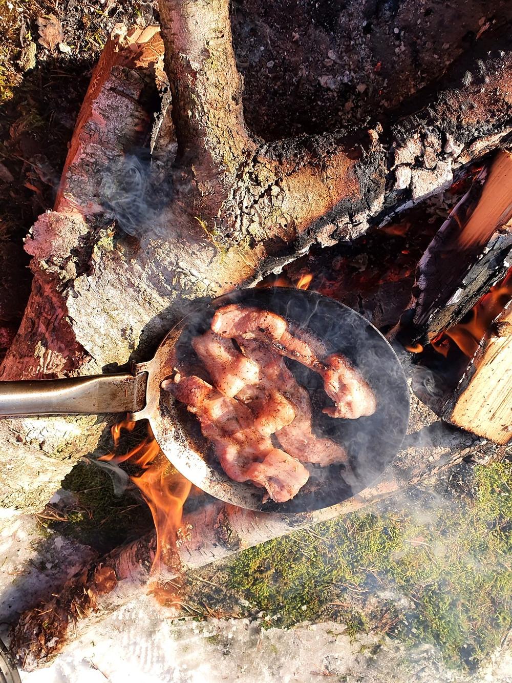stekfläsk i panna över öppen eld