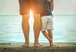 Father and son stay on the sea beach und