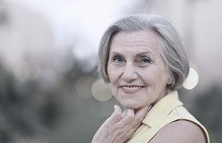 lächelnde glückliche Seniorin in der Stadt
