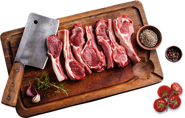 Wooden butcher block with lamb chops, spices, and tomatoes | Mona's Fine Meats