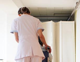 福岡にある花畑病院での患者さまの車いすを押す看護師の様子