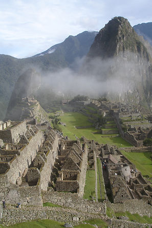An overview of Machu Picchu with some clouds blanketing the tops of the background ruins taken on one of The Alpaca Guy's Peru trips.
