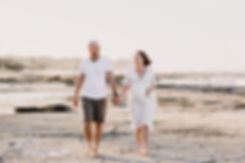 Pregnant mother and father walking along the beach holding hands