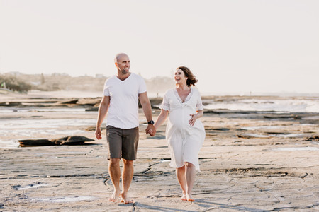 Man and woman walking along the beach holding hands