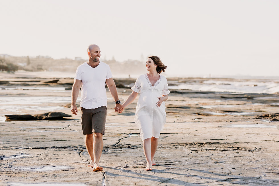Father and pregnant mother walking along beach holding hands