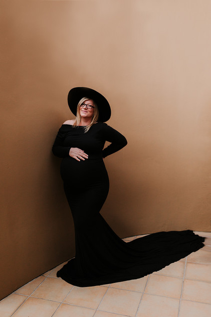 Photo of pregnant woman wearing a black dress and black hat