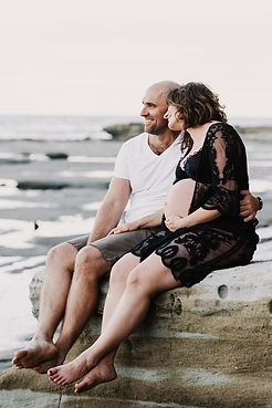 Pregnant woman sitting with the father on a rock at a beach