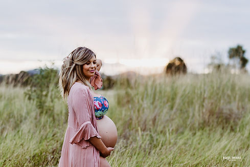 Pregnant woman standing in a field with her belly exposed