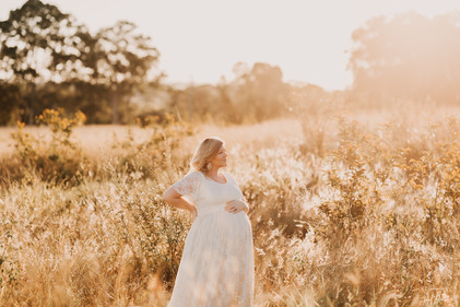 Woman standing in a sunlit field holding her pregnant belly