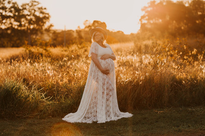 Pregnant woman in a field at sunset holding her belly