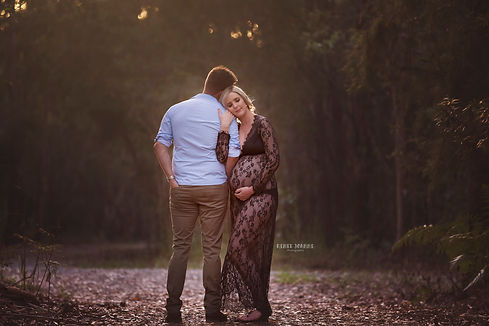 Pregnant Woman in forest hugging the father