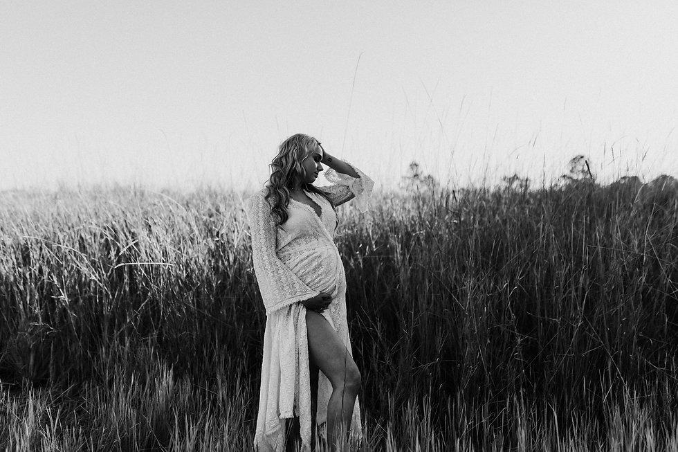 Maternity photo in a grassy field