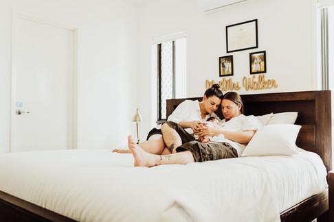 Mum and Dad on their bed cuddling newborn baby