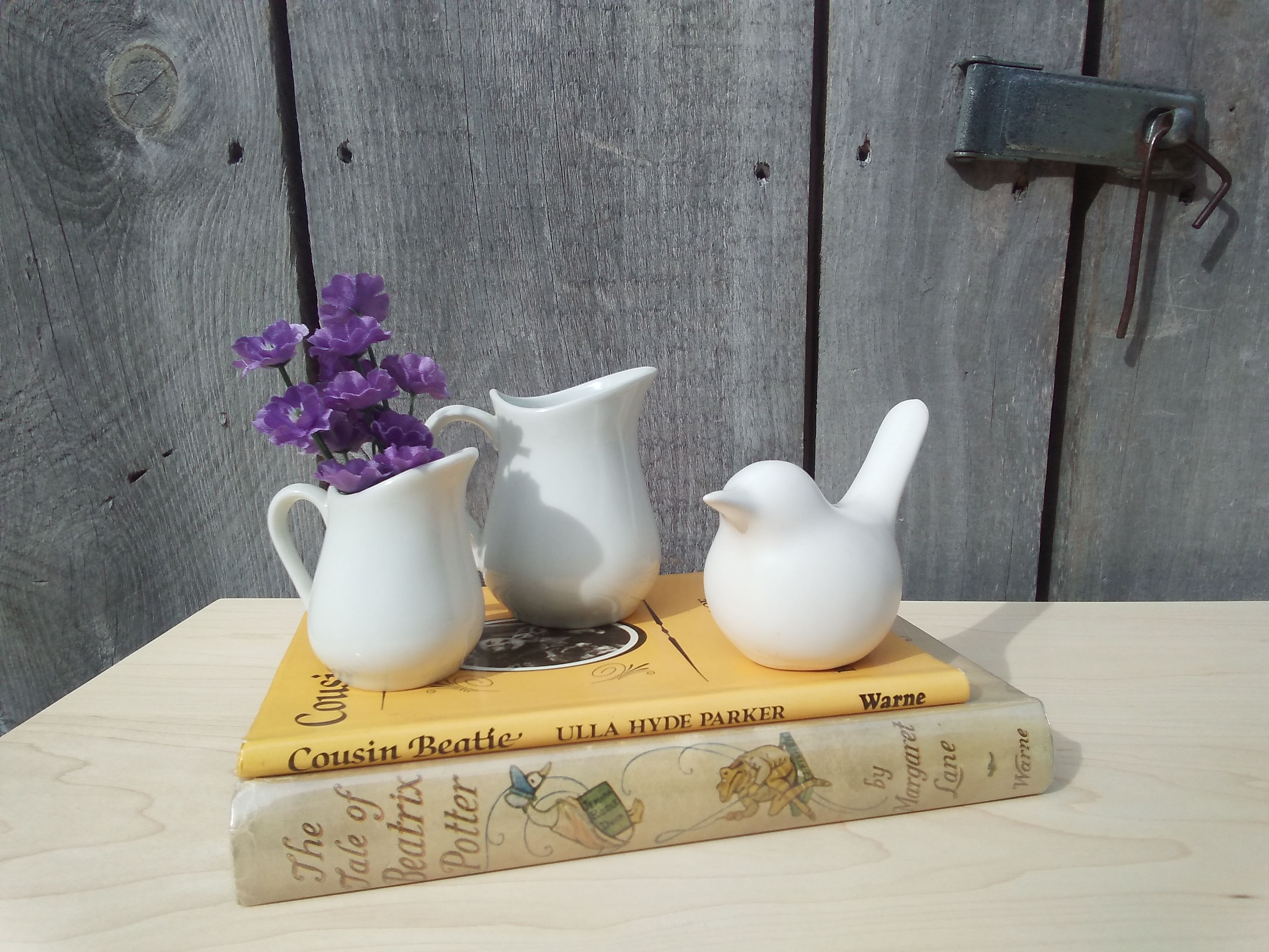 Ironstone pitchers and white ceramic bird