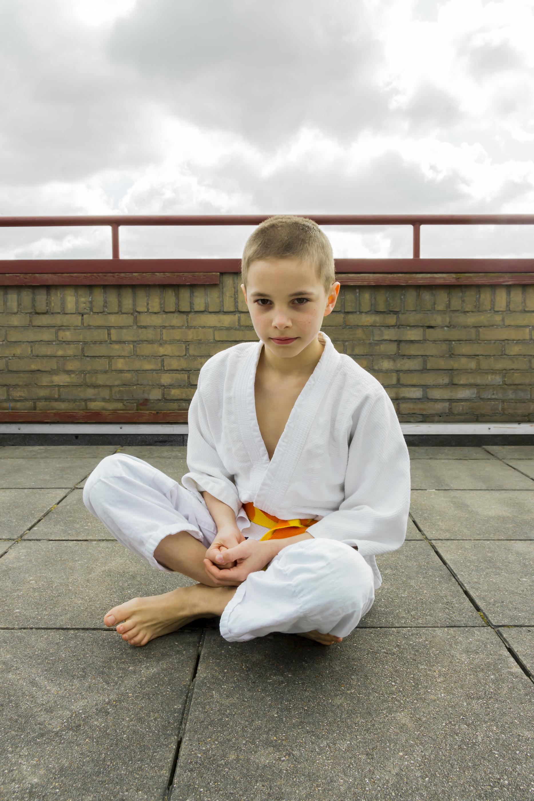 Judoka Teen Boy Sitting On The Roof (sky Background)
