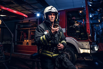 The fire brigade arrived at the night-time. Fireman in a protective uniform standing next