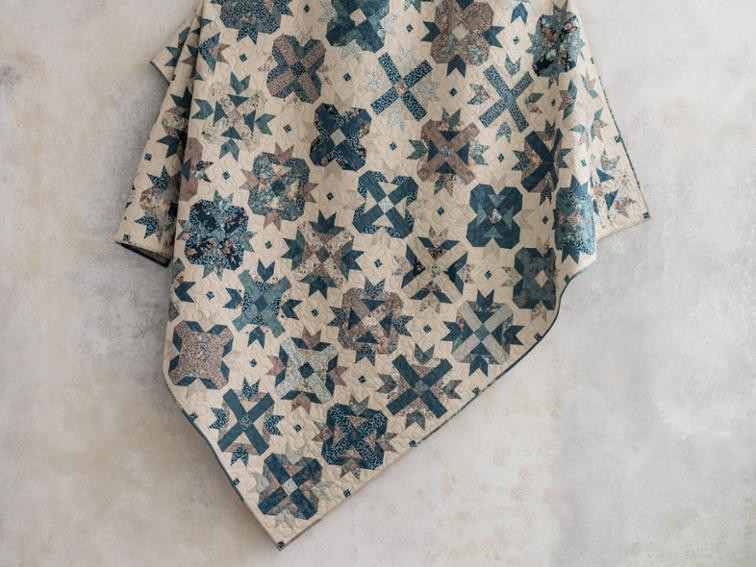 A cream, light browns and steely blues patchwork quilt.