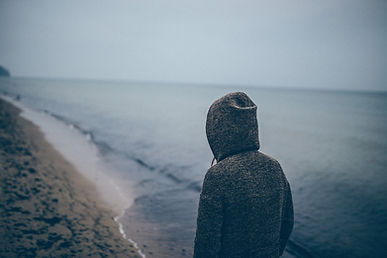 Person standing at the edge of the ocean water