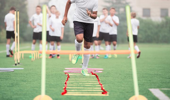 Fußballer läuft durch Koordinationsleiter