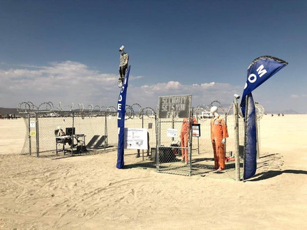 This satirical installation showed an office space and a living room surrounded by barbed wire, security cameras, and people in orange jumpsuits. A TV commercial boasting of this secure way of living played on loop in the centre.