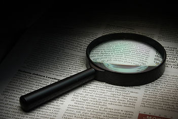 Magnifying glass and article.