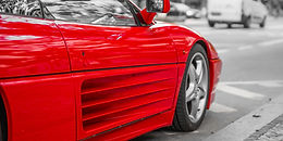 Red sports car on city streets, black an