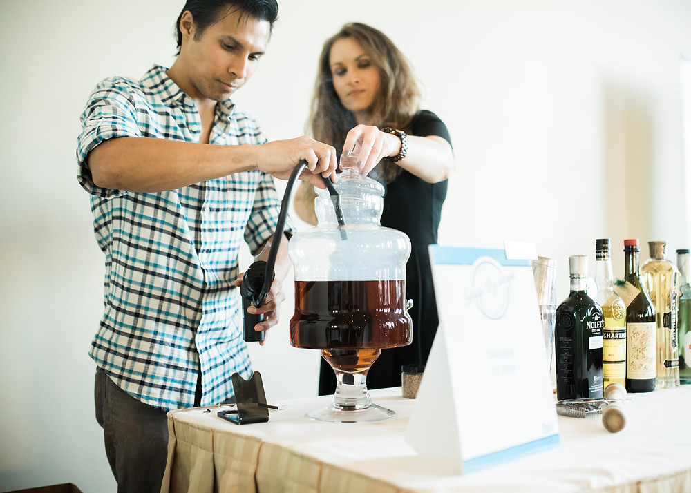 Big Orange mixologist Luiggi Uzcategui uses fire to prepare his signature cocktail for Thea Foundation's Blue Plate Special 2017