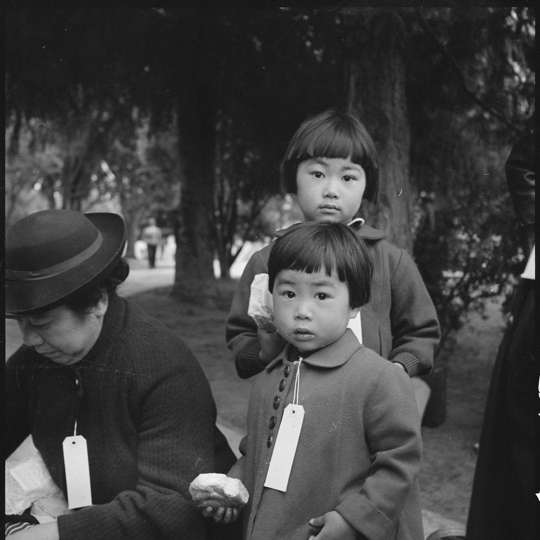 Two children from the Mochida family in Hayward, California wait for the bus that will take them to concentration camp.