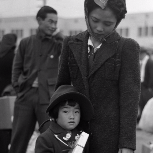 A Japanese American mother and daughter awaiting train during evacuation, Los Angeles, California.
