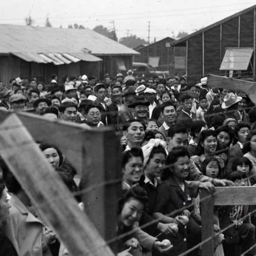 Crowd of Japanese Americans stand behind a barbed wire fence waving to departing friends on train leaving Santa Anita, California.