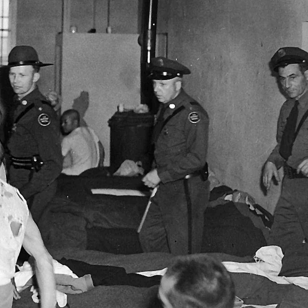 Japanese-American prisoner being forcefully escorted from the Barracks Mess Hall.
