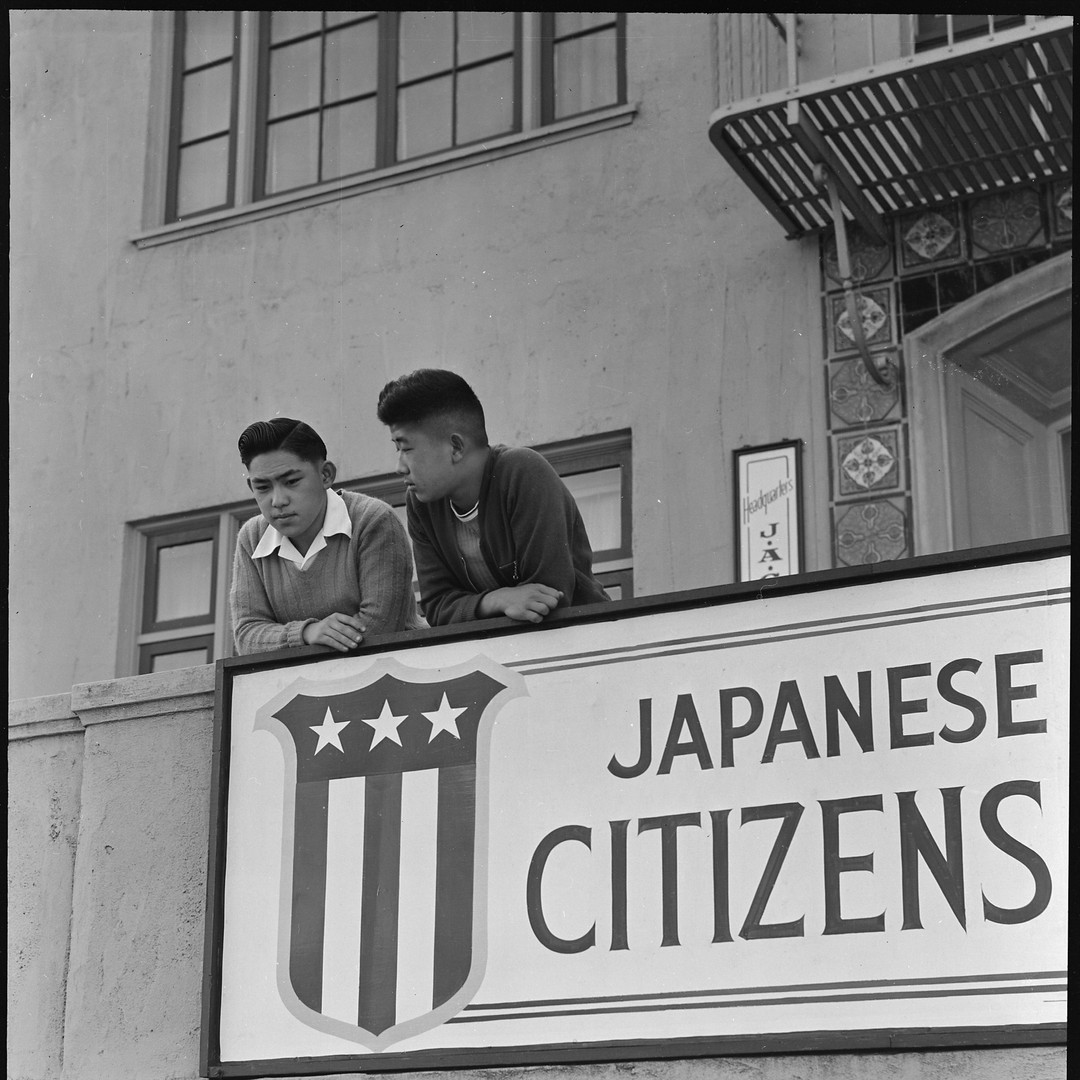 High school boys on the balcony of the Japanese American Citizens League watching friends board evacuation buses. San Francisco, 1942.