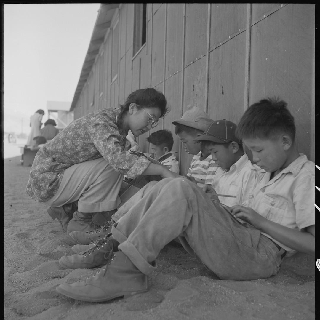 School children study outside under the shade at Manzanar War Relocation Center, California.
