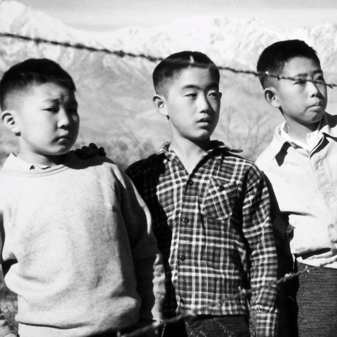Three boys behind barbed wire enclosure at Manzanar War Relocation Center near Lone Pine, California.