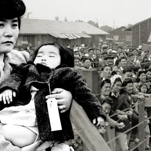 A woman holds her daughter as they prepare to leave home for an internment camp.