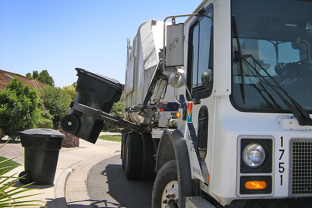 Waste removal truck collecting garbage