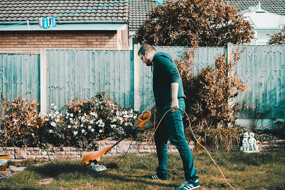 Man gardening with weed whacker in backyard