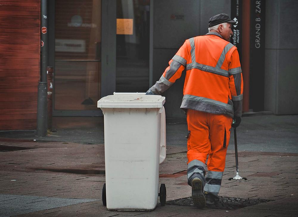 Waste worker pulling a dustbin
