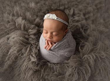 newborn girl in potato sack pose on grey